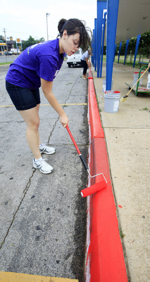 Photo - VOLUNTEER: Melissa Urban, Teach for America teacher, painting the curb in front of Roosevelt Middle School in Oklahoma City Friday, June 10, 2011. Teach for America teachers were volunteering at Roosevelt to do painting and landscape work. Melissa will be teaching eighth grade math at Webster Middle School next fall. Photo by Paul B. Southerland, The Oklahoman ORG XMIT: KOD
