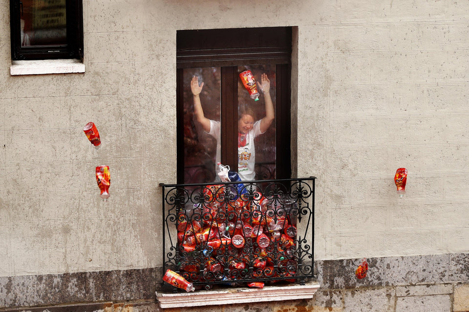 Photo - Revelers throws empty wine bottles to fill up a balcony during the launch of the 'Chupinazo' rocket, to celebrate the official opening of the 2014 San Fermin fiestas, in Pamplona, Spain, Sunday, July 6, 2014. Revelers from around the world kick off the festival with a messy party in the Pamplona town square, one day before the first of eight days of the running of the bulls glorified by Ernest Hemingway's 1926 novel