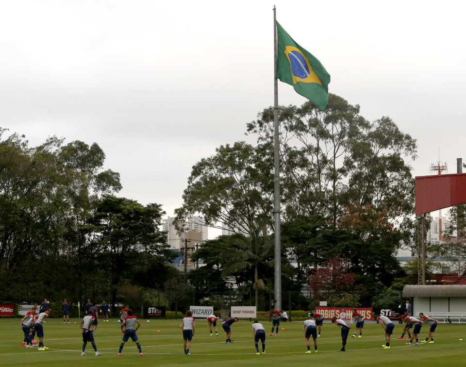 Photo - United States players stretch at the beginning of a training session as a Brazilian flags flies in the background, at the Sao Paulo FC training center in Sao Paulo, Brazil, Monday, June 9, 2014. The U.S. will play in group G of the 2014 soccer World Cup. (AP Photo/Julio Cortez)