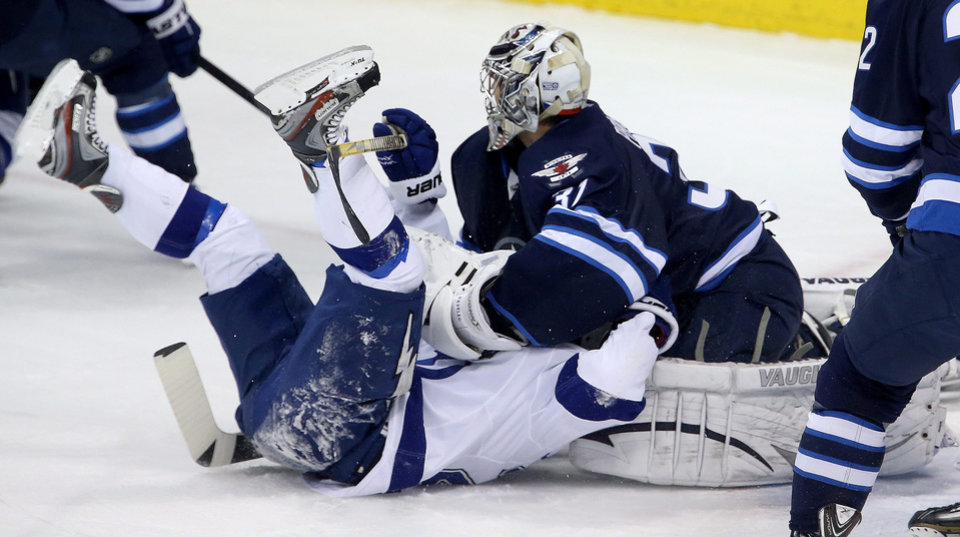 Photo - Tampa Bay Lightning's Martin St. Louis (26) is smothered by Winnipeg Jets goaltender Ondrej Pavelec (31) during the first period of an NHL hockey game Tuesday, Jan. 7, 2014, in Winnipeg, Manitoba. (AP Photo/The Canadian Press, Trevor Hagan)