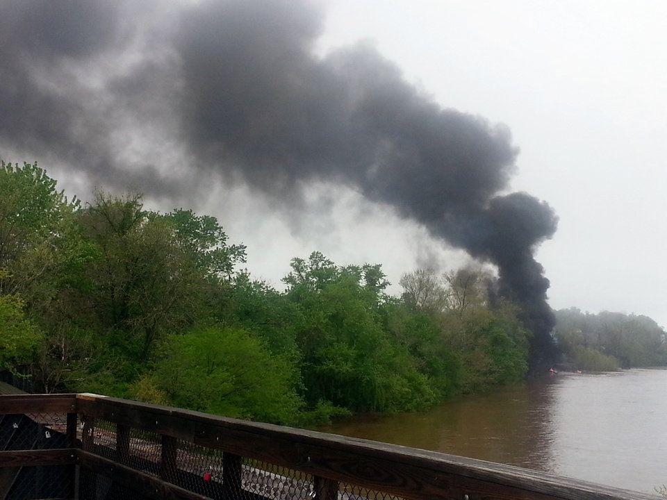 Photo - This mobile phone photo provided Ali Hallock shows smoke rising after several CSX tanker cars carrying crude oil derailed, from the view of a bridge over the James river, Wednesday, April 30, 2014, in Lynchburg, Va. Authorities evacuated numerous buildings Wednesday after the derailment. (AP Photo/Ali Hallock) MANDATORY CREDIT