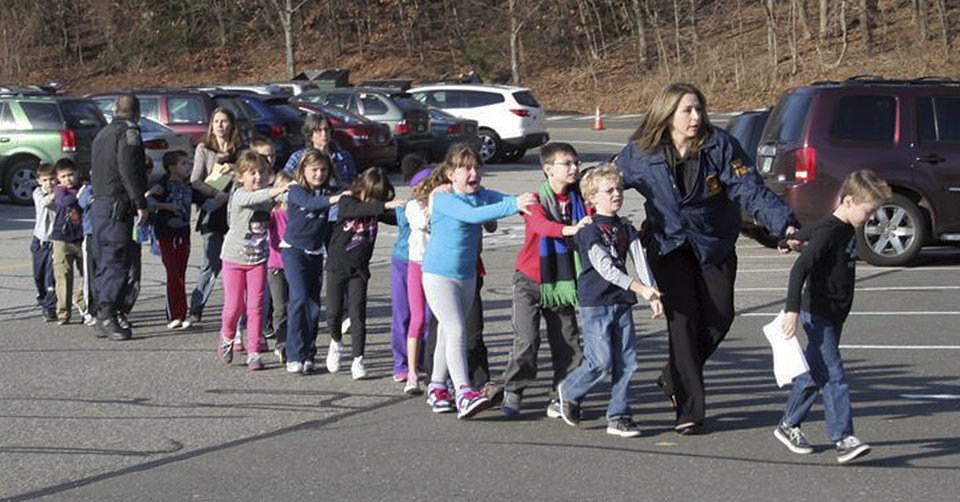 Photo - In this photo provided by the Newtown Bee, Connecticut State Police lead children from the Sandy Hook Elementary School in Newtown, Conn., following a reported shooting there Friday, Dec. 14, 2012.  (AP Photo/Newtown Bee, Shannon Hicks)  MANDATORY CREDIT