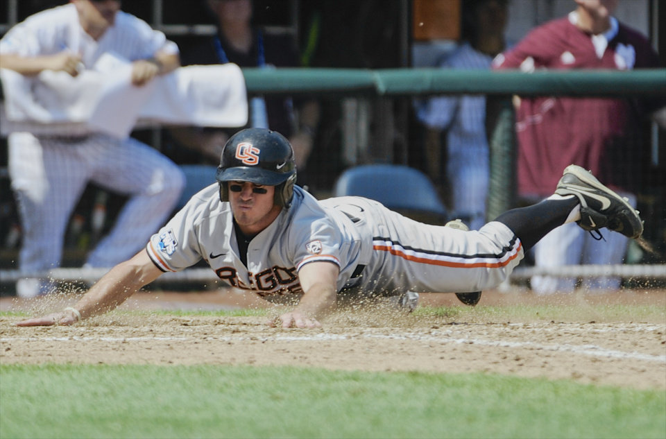 Photo - Oregon State's Max Gordon scores at home plate against Mississippi State on a single by Andy Peterson in the sixth inning of an NCAA College World Series baseball game in Omaha, Neb., Friday, June 21, 2013. (AP Photo/Francis Gardler)