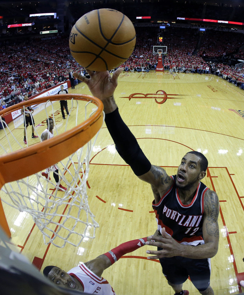 Photo - Portland Trail Blazers' LaMarcus Aldridge (12) goes up for a shot against the Houston Rockets during the second half in Game 1 of an opening-round NBA basketball playoff series Sunday, April 20, 2014, in Houston. The Trail Blazers won 122-120 in overtime. (AP Photo/David J. Phillip)