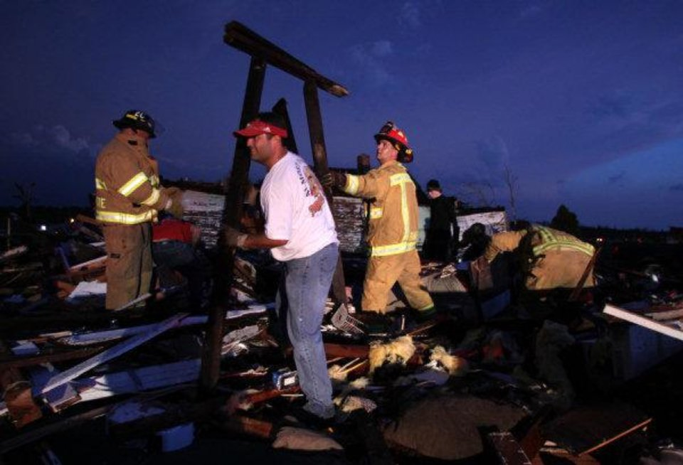 Photo - Volunteers and firefighters from Grove Township, Kan., look through the wreckage of a destroyed homes in Joplin, Mo., Sunday, May 22, 2011. A large tornado moved through much of the city, damaging a hospital and hundreds of homes and businesses. (AP Photo/Mark Schiefelbein) ORG XMIT: MOMS112