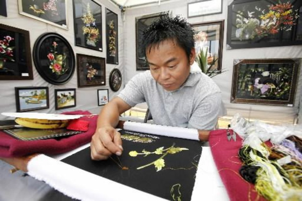 Photo -  Silk embroidery artist Don Tran works on a piece inside his booth during the Paseo Arts Festival in Oklahoma City, OK, Saturday, May 26, 2012, By Paul Hellstern, The Oklahoman Archives