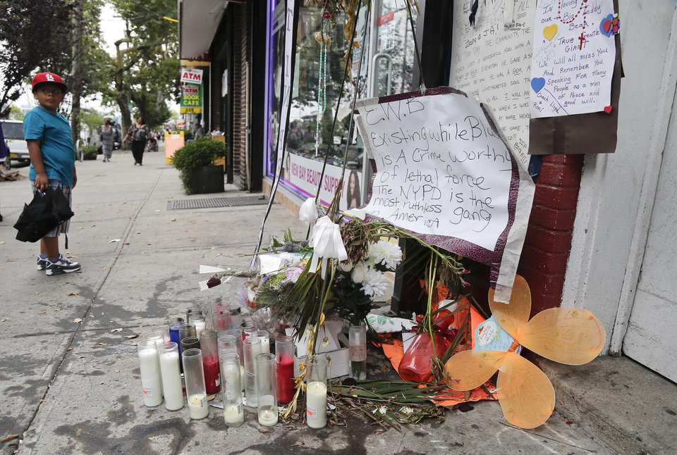 Photo - A young boy stops as he passes a makeshift memorial for Eric Garner, Friday, Aug. 1, 2014, in the Staten Island borough of New York. Garner was put in a chokehold while being arrested at the site last month for selling untaxed loose cigarettes. On Friday, the medical examiner ruled Garner's death to be a homicide caused by a police chokehold. (AP Photo/Julie Jacobson)