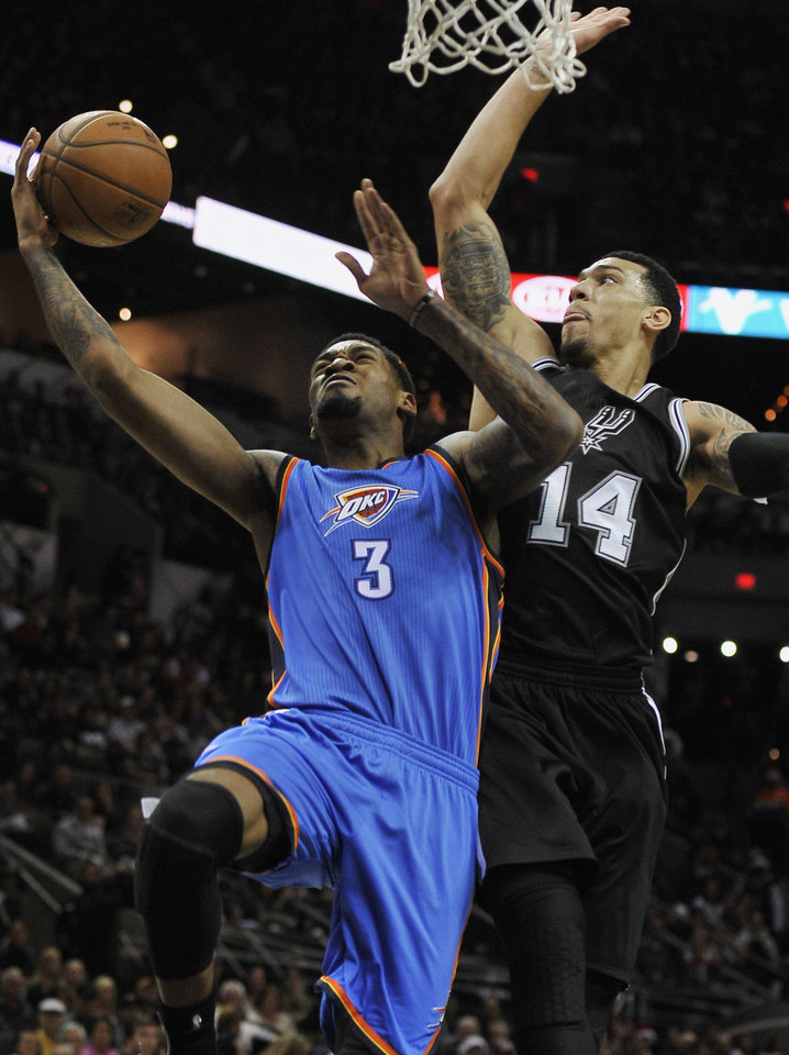 Photo - Oklahoma City Thunder forward Perry Jones (3) shoots against San Antonio Spurs guard Danny Green during the first half an NBA basketball game, Thursday, Dec. 25, 2014, in San Antonio. (AP Photo/Darren Abate)
