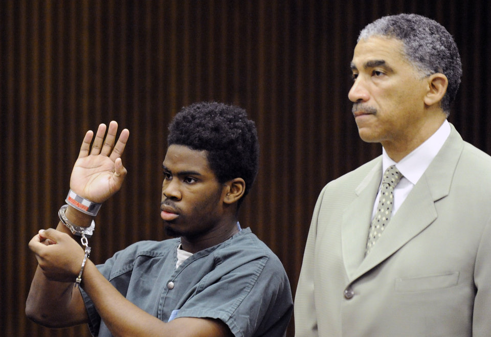 Photo - Defendant Bruce Wimbush, Jr., standing with his defense attorney Randall Upshaw, takes a plea deal before Judge James Callahan at Frank Murphy Hall of Justice in Detroit on Monday June 16, 2014. Wimbush has pleaded guilty in the Detroit mob beating of a motorist who accidentally struck a child with his pickup. (AP Photo/The Detroit News, David Coates)