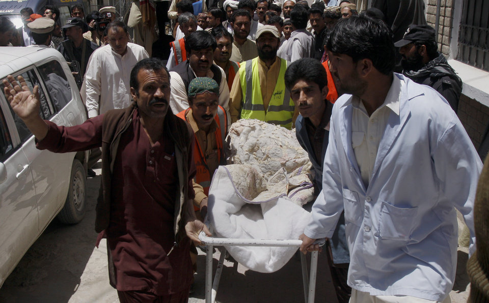 Photo -   Pakistani volunteers and hospital staff transport the body of British Red Cross worker Khalil Rasjed Dale at a local hospital in Quetta, Pakistan on Sunday, April 29, 2012. The body of a British Red Cross worker held captive in Pakistan since January was found in an orchard Sunday, his throat slit and a note attached to his body saying he was killed because no ransom was paid, police said. (AP Photo/Arshad Butt)