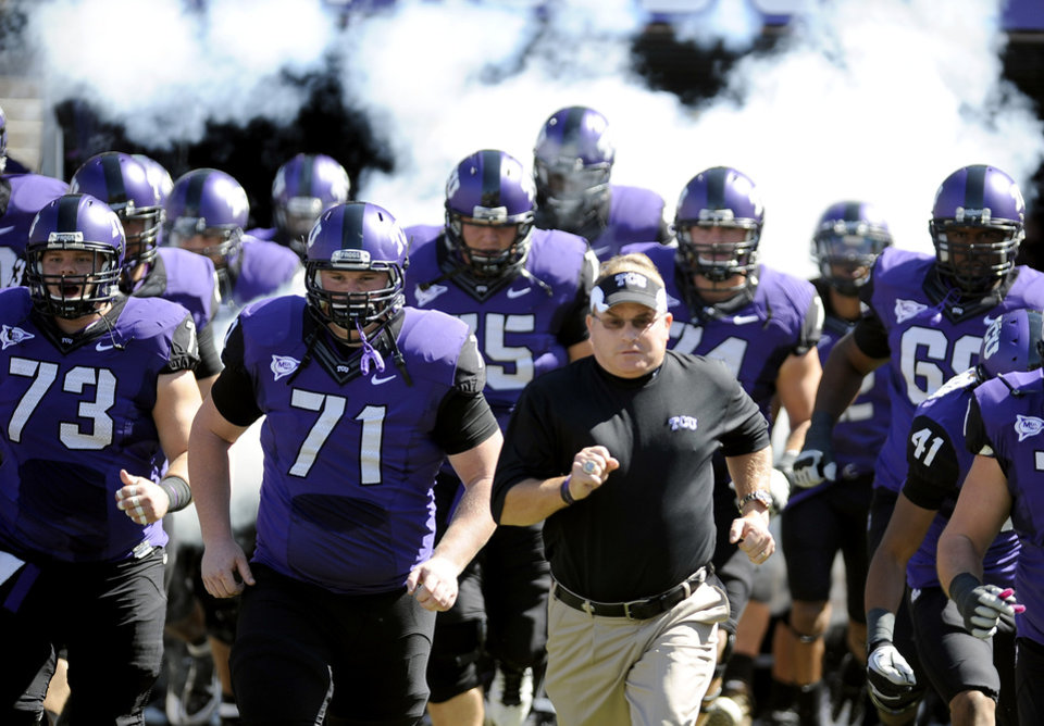 Photo - In this photo taken Saturday, Oct. 1, 2011, TCU head coach Gary Patterson runs onto the field with his team before an NCAA college football game against SMU in Fort Worth, Texas. Leaders of the Big 12 Conference cleared the way Thursday, Oct. 6, 2011, to add TCU, a move that would bring in a rising program and potentially shore up a league that seemed ready to fall apart just a few weeks ago. (AP Photo/Matt Strasen) ORG XMIT: NY169