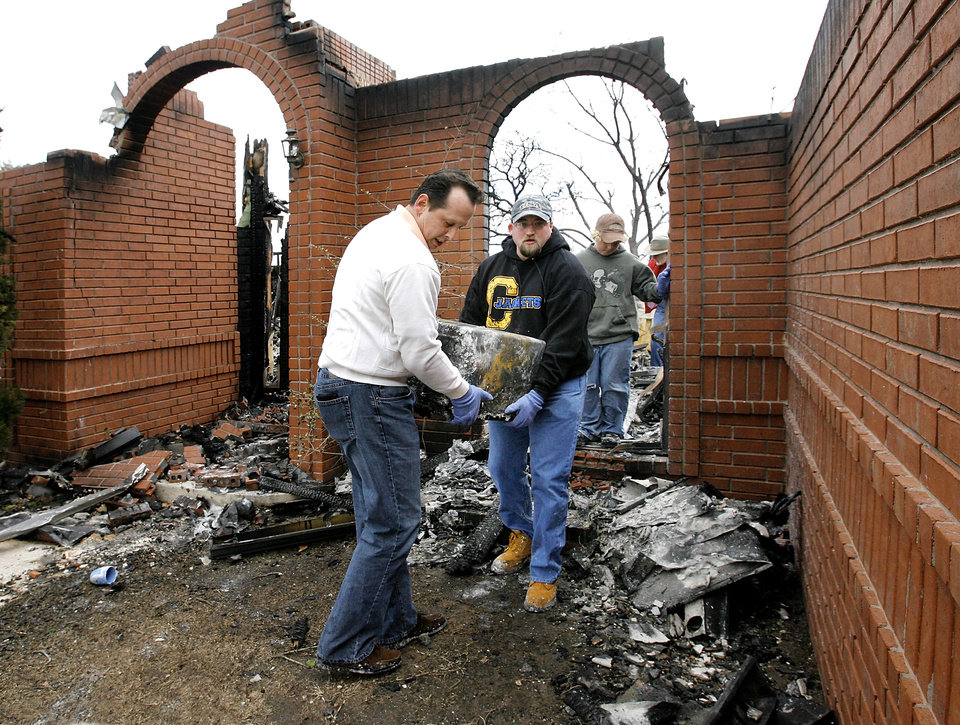 Shawn Garza, left, and Robert Tanksley, Jr. remove a safe from the home of Tanksley's parents, 2024 Camelot in Oakwood East Royale neighborhood Friday morning, April 10, 2009.  The house was destroyed in Thursday's wildfires.  No one was injured in the fire.  Photo by Jim Beckel, The Oklahoman