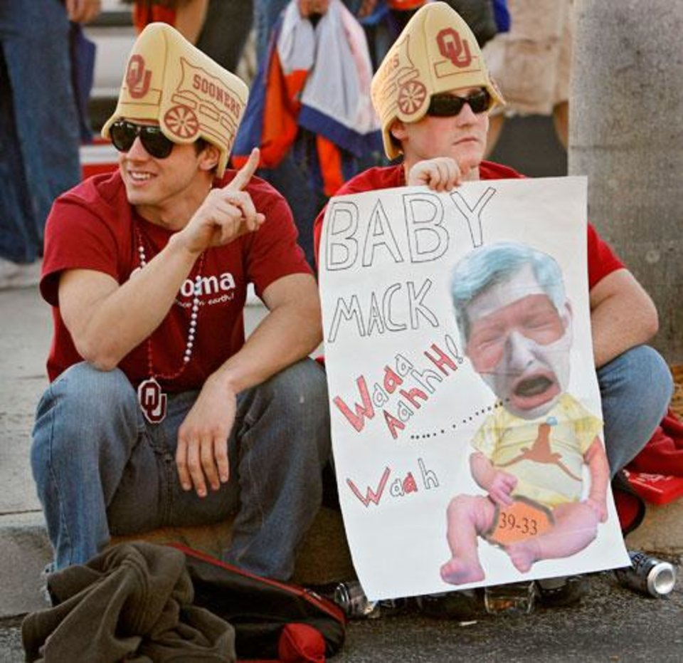 Photo -  Sooner fans William Winfree and Andrew Hajek, from left, sit on the curb as they wait to get in the gates before the BCS National Championship college football game between the University of Oklahoma Sooners (OU) and the University of Florida Gators (UF) on Thursday, Jan. 8, 2009, at Dolphin Stadium in Miami Gardens, Fla.   PHOTO BY CHRIS LANDSBERGER, THE OKLAHOMAN