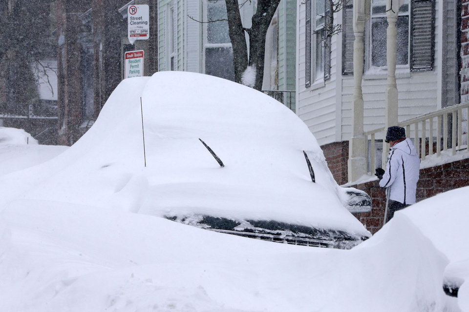 Photo - A woman shovels out a car on Third street in the South Boston neighborhood of Boston on Saturday, Feb. 9, 2013. A behemoth storm packing hurricane-force wind gusts and blizzard conditions swept through the Northeast overnight. (AP Photo/Gene J. Puskar)