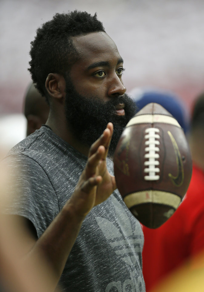 Photo - James Harden of the Houston Rockets tosses a football on the Houston sideline during the AdvoCare Texas Kickoff college football game between the University of Oklahoma Sooners (OU) and the Houston Cougars at NRG Stadium in Houston, Saturday, Sept. 3, 2016. Photo by Nate Billings, The Oklahoman