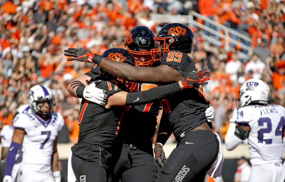 Photo - Oklahoma State celebrates a Dillon Stoner (17) touchdown in the first quarter during the college football game between the Oklahoma State University Cowboys and the TCU Horned Frogs at Boone Pickens Stadium in Stillwater, Okla.,  Saturday, Nov. 2, 2019. [Sarah Phipps/The Oklahoman]