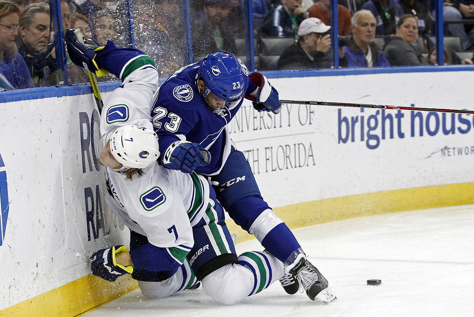 Photo - FILE - In this March 17, 2014, file photo, Tampa Bay Lightning right wing J.T. Brown (23) checks Vancouver Canucks left wing David Booth (7) as they battle for the puck during the first period of an NHL hockey game in Tampa, Fla. For the first time since 1973, there is just one Canadian team in the NHL postseason. The Montreal Canadiens represent the nation's only hope of ending a 21-year Stanley Cup drought. (AP Photo/Brian Blanco, File)