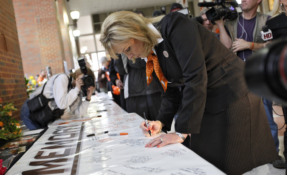 Photo - Gov. Mary Fallin signs the memory banner during the memorial service for Oklahoma State head basketball coach Kurt Budke and assistant coach Miranda Serna at Gallagher-Iba Arena on Monday, Nov. 21, 2011 in Stillwater, Okla. The two were killed in a plane crash along with former state senator Olin Branstetter and his wife Paula while on a recruiting trip in central Arkansas last Thursday. Photo by Chris Landsberger, The Oklahoman