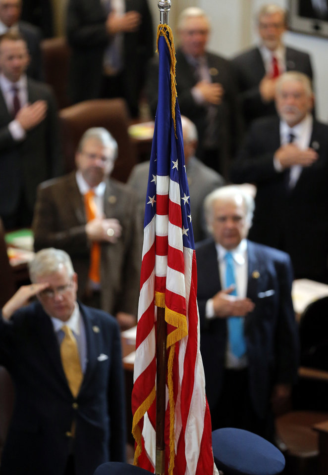 Photo - Legislators salute the American Flag at the start of the Oklahoma Legislature's 2016 State-of-the-State Address by Gov. Mary Fallin in the chamber of the House of Representatives at the Oklahoma state capitol on Monday, Feb. 1, 2016, in Oklahoma City, Okla. Photo by Chris Landsberger, The Oklahoman