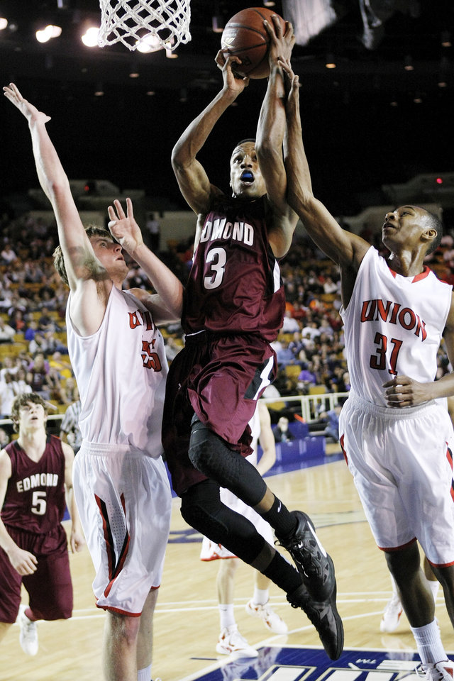 Edmond Memorial's James Woodard (3) shoots between Union's Yuri Hager (55) and Sedrick Johnson (31) during the Class 6A boys high school basketball state tournament championship game between Edmond Memorial and Tulsa Union at the Mabee Center in Tulsa, Okla., Saturday, March 10, 2012. Photo by Nate Billings, The Oklahoman