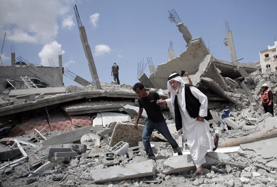 Photo - An elderly Palestinian man makes his way on the rubble of a destroyed house following Israeli strikes in Rafah refugee camp, southern Gaza Strip, Monday, Aug. 4, 2014. (AP Photo/Khalil Hamra)