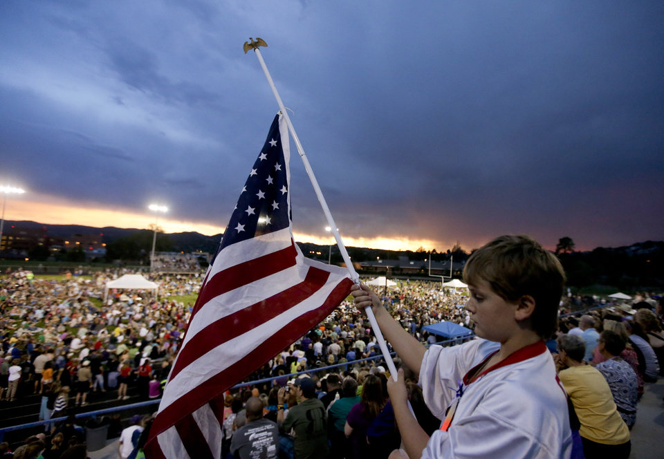 Photo - Ty Green, 9, holds a United States flag during a community vigil on Tuesday, July 2, 2013.  in Prescott, Ariz. for the 19 firefighters from Granite Mountain Interagency Hotshot Crew that were killed battling a wildfire near Yarnell, Ariz. The elite crew of firefighters were overtaken by the out-of-control blaze as they tried to protect themselves from the flames under fire-resistant shields on Sunday. (AP Photo/Chris Carlson)