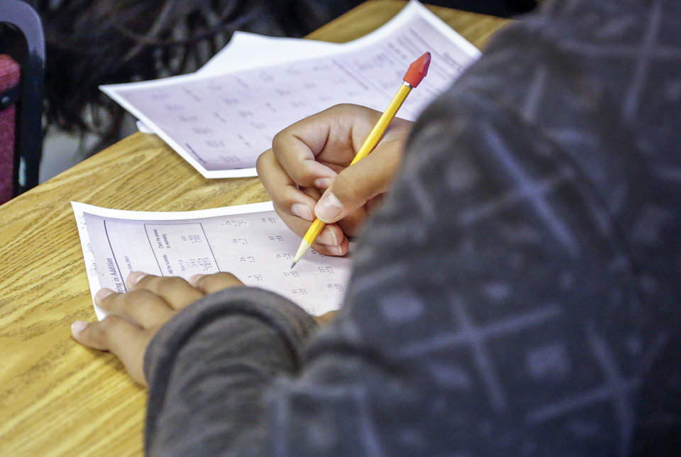 Photo -  A student works on math May 12 in the Latino Community Development Agency's Alternative to Suspension classroom.