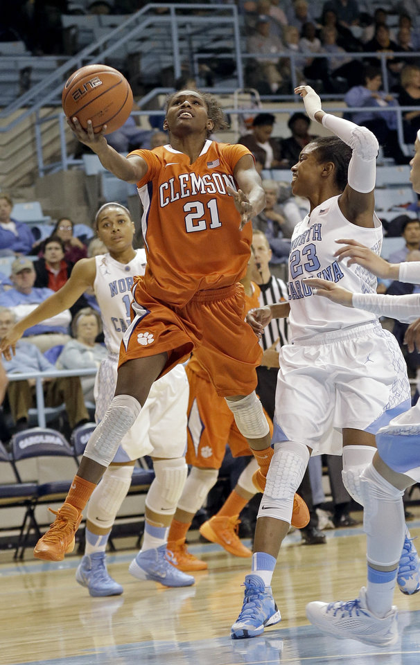 Photo - Clemson's Nikki Dixon (21) drives to the basket as North Carolina's Diamond DeShields (23) defends during the second half of an NCAA college basketball game in Chapel Hill, N.C., Thursday, Jan. 16, 2014. North Carolina won 78-55. (AP Photo/Gerry Broome)