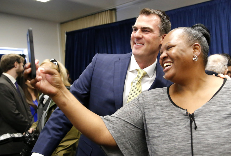 Photo - Joy Block takes a photograph with Gov. Kevin Stitt after the Pardon and Parole Board read the names of 527 Oklahoma inmates recommend for commutation at the Kate Barnard Correctional Center in Oklahoma City, Friday, Nov. 1, 2019. Block was formerly incarcerated and now with with the Walter's Way Regaining Your Life Foundation. [Sarah Phipps/The Oklahoman]