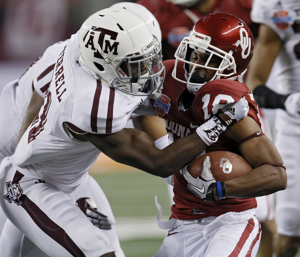 Texas A&M\'s Steven Terrell (21) brings down Oklahoma\'s Jalen Saunders (18) during the college football Cotton Bowl game between the University of Oklahoma Sooners (OU) and Texas A&M University Aggies (TXAM) at Cowboy\'s Stadium on Friday Jan. 4, 2013, in Arlington, Tx. Photo by Chris Landsberger, The Oklahoman