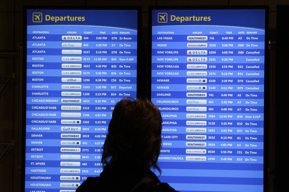 FILE - This Oct. 31, 2012 file photo shows a passenger checking the departures board at Pittsburgh International Airport in Imperial, Pa. as air travel creaked back to normal following last fall's Superstorm Sandy, which caused severe disruptions in air travel. Experts say travelers planning cruises who are dependent on flights to get them to their departure ports might consider travel insurance to cover problems like missed flights that could impact their trips. (AP Photo/Gene J. Puskar, file)
