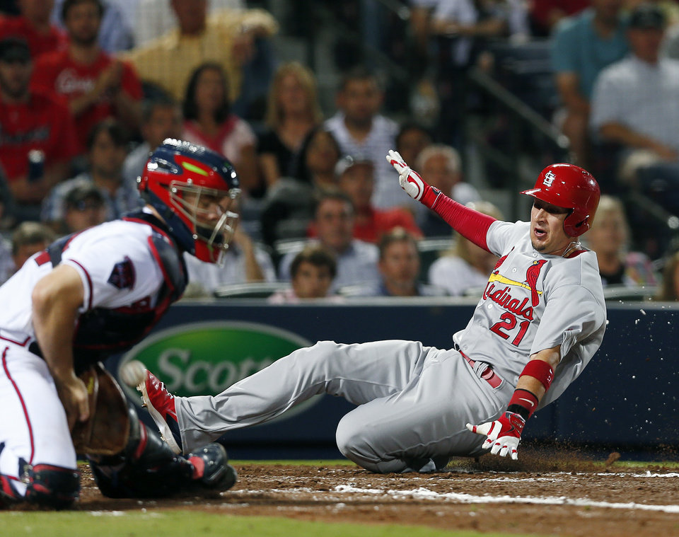 Photo - St. Louis Cardinals right fielder Allen Craig (21) scores on a Peter Bourjos (8) base hit as Atlanta Braves catcher Evan Gattis (24) handles the late throw in the sixth inning of a baseball game Monday, May 5, 2014 in Atlanta.  (AP Photo/John Bazemore)