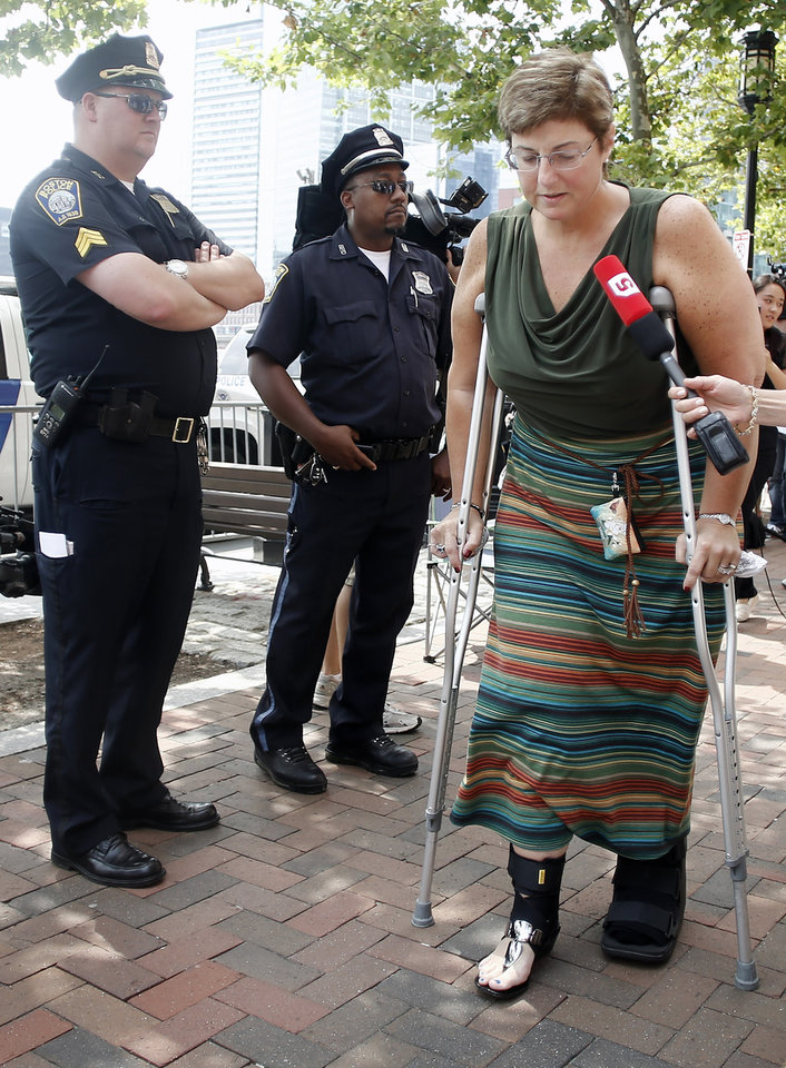 Photo - Boston Marathon bombing victim Karen Brassard makes her way into the federal courthouse for the arraignment of bombing suspect Dzhokhar Tsarnaev Wednesday, July 10, 2013, in Boston. The April 15 attack killed three and wounded more than 260. The 19-year-old Tsarnaev has been charged with using a weapon of mass destruction, and could face the death penalty. (AP Photo/Winslow Townson)