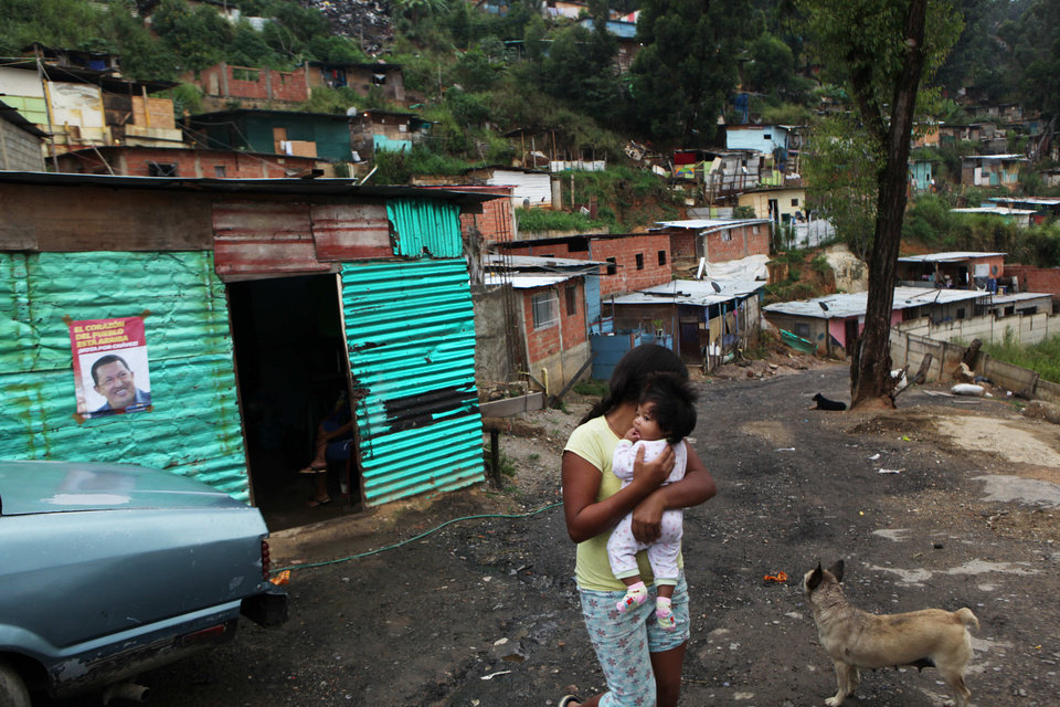 A girl carries a baby along a street lined with homes built with metal sheets and cinder blocks, where a poster of Venezuela's President Hugo Chavez hangs, left, in Caracas, Venezuela, Friday, Oct. 5, 2012. Venezuelans will head to the polls Sunday to vote in their country's presidential election, deciding on whether to keep President Hugo Chavez or seek change. (AP Photo/Rodrigo Abd)