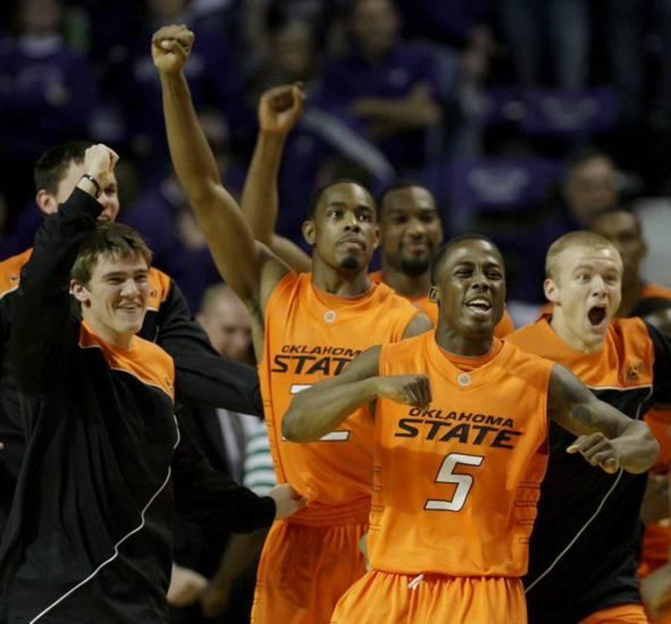 Photo - Oklahoma State players celebrate after upsetting tenth-ranked Kansas State in an NCAA college basketball game Saturday, Jan. 23, 2010 in Manhattan, Kan. Oklahoma State won the game 73-69. (AP Photo/Charlie Riedel)