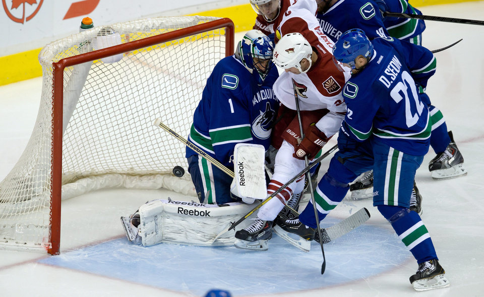 Photo - Phoenix Coyotes' Kyle Chipchura centre, kicks the puck into the net past Vancouver Canucks' goalie Roberto Luongo, left, as Daniel Sedin, right, of Sweden, defends during the second period of an NHL hockey game in Vancouver, British Columbia, on Sunday, Jan. 26, 2014. (AP Photo/The Canadian Press, Darryl Dyck)