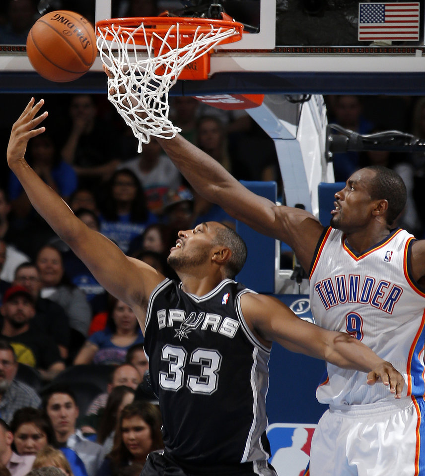 Photo - Oklahoma City's Serge Ibaka (9) defends San Antonio's Boris Diaw (33) during an NBA basketball game between the Oklahoma City Thunder and the San Antonio Spurs at Chesapeake Energy Arena in Oklahoma City, Thursday, April 3, 2014. Oklahoma City won 106-94. Photo by Bryan Terry, The Oklahoman