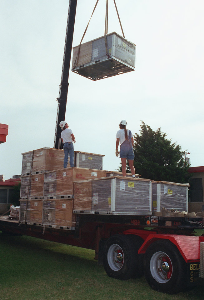 Photo - An air conditioning unit is craned into place on the roof of Willow Brook Elementary School at 8105 NE 10.  Twenty-three units, ranging from 3 to 10 tons, were placed on the roof on 7/17/97.   Workers Lew Homme and Jo Arrington watch the unit