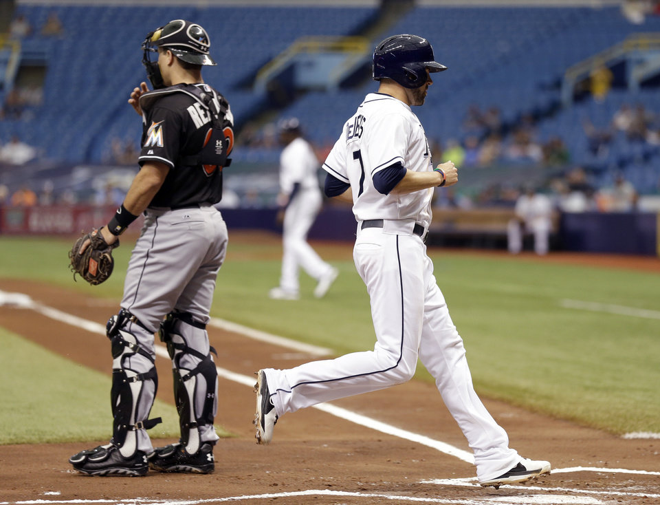 Photo - Tampa Bay Rays' David DeJesus, right, scores past Miami Marlins catcher Jacob Realmuto on a sacrifice fly by teammate James Loney during the first inning of an interleague baseball game Thursday, June 5, 2014, in St. Petersburg, Fla. (AP Photo/Chris O'Meara)
