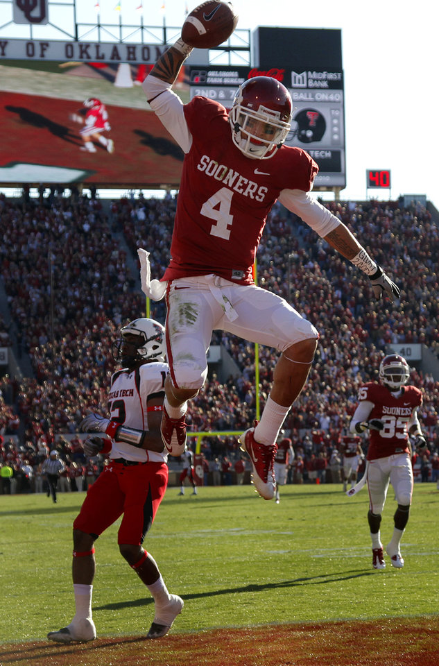 Photo - Oklahoma's Kenny Stills (4) spikes the ball after a touchdown reception during the first half of the college football game between the University of Oklahoma Sooners (OU) and the Texas Tech Red Raiders (TTU) at the Gaylord Family Memorial Stadium on Saturday, Nov. 13, 2010, in Norman, Okla.  Photo by Chris Landsberger, The Oklahoman