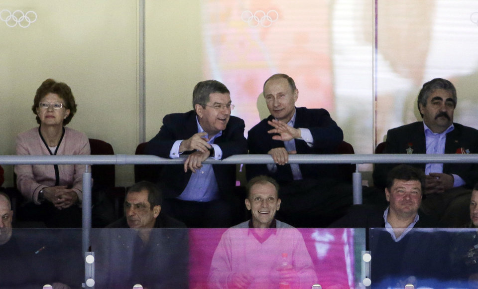 Photo - Russian President Vladimir Putin, center right, talks with IOC President Thomas Bach while watching the USA Russia men's hockey game from a box at the 2014 Winter Olympics, Saturday, Feb. 15, 2014, in Sochi, Russia. (AP Photo/David J. Phillip )