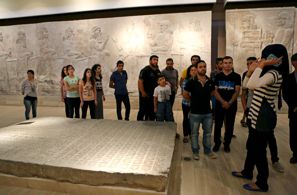 Photo - People invited for a ceremony inaugurating two renovated halls, visit the Iraqi National Museum, in Baghdad, Iraq, Thursday, Aug. 21, 2014. Two renovated halls adorned mainly with rare life-size stone statues were inaugurated at the Iraqi National Museum on Thursday geared toward honoring the 5,000 year legacy of the ancient city of Hatra. (AP Photo/Hadi Mizban)
