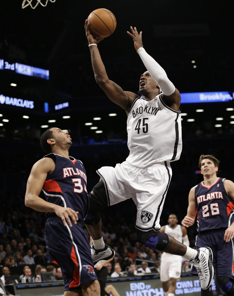Brooklyn Nets forward Gerald Wallace (45) goes up for a layup in front of Atlanta Hawks guard Devin Harris (34) as Hawks guard Kyle Korver (26) watches from the floor in the first half of their NBA basketball game at the Barclays Center, Friday, Jan. 18, 2013, in New York. (AP Photo/Kathy Willens)