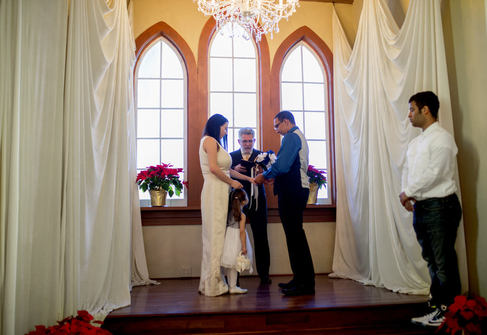 Photo -   Alicia Wesley and Presten McCalip, both 17, exchange vows in front of minister John T. Snelson V and Wesley's daughter, Raydeeian Graham, 2, as best man Torree Coone stands during their wedding Dec. 28 in Oklahoma City. [Photo by Bryan Terry, The Oklahoman]