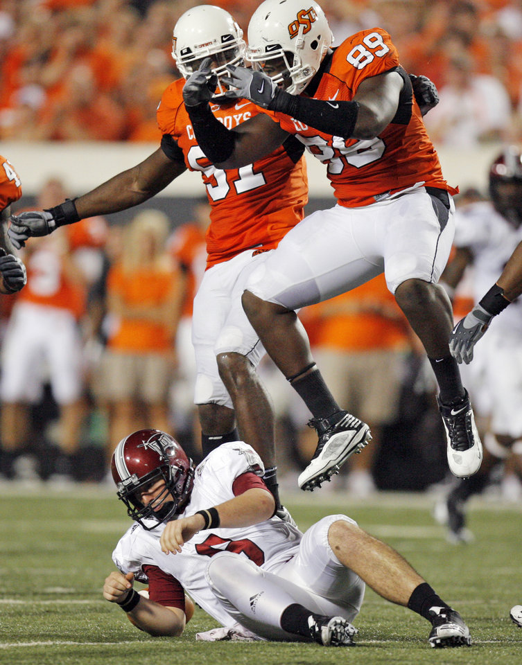 Photo - OSU's Ugo Chinasa (91) and Nigel Nicholas (89) celebrate a sack of Troy quarterback Corey Robinson (6) in the third quarter during the college football game between the Oklahoma State University Cowboys (OSU) and the Troy University Trojans at Boone Pickens Stadium in Stillwater, Okla., Saturday, Sept. 11, 2010. OSU won, 41-38. Photo by Nate Billings, The Oklahoman