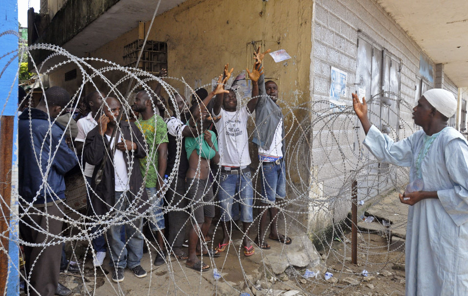 Photo - A man, right, working for a humanitarian group, throws water in a small bag to West Point residents behind the fence of a holding area, as they wait for a second consignment of food from the Liberian Government to be handed out, at the West Point area, near the central city area of Monrovia, Liberia, Friday, Aug. 22, 2014. Two new cases of Ebola have emerged in Nigeria and, in an alarming development, they are outside the group of caregivers who treated an airline passenger who arrived with Ebola and died, Health Minister Onyebuchi Chukwu said Friday.(AP Photo/Abbas Dulleh)