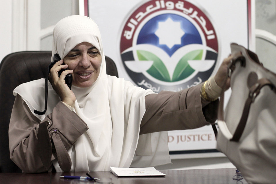 In this Wednesday, Oct. 9, 2012 photo, Azza el-Gharf of the Muslim Brotherhood's Freedom and Justice Party talks on her mobile phone at the party's office in Cairo, Egypt. El-Garf, a 47-year-old mother of seven who joined the Brotherhood when she was 15, said that a woman�s role in her family need not contradict with her participation in politics, saying that she balances these two responsibilities. The rise of the Muslim Brotherhood to power in Egypt has brought with it a new group of female politicians who say they are determined to bring more women into leadership roles _ and at the same time want to consecrate a deeply conservative Islamic vision for women in Egypt.(AP Photo/Maya Alleruzzo)