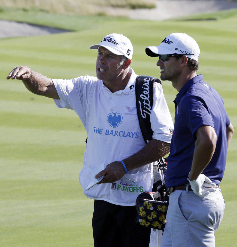 Photo - Caddie Stevie Williams, left, talks to Adam Scott, of Australia, on the 18th hole during the final round of The Barclays golf tournament on Sunday, Aug. 25, 2013, in Jersey City, N.J. Scott won the tournament2. (AP Photo/Mel Evans)