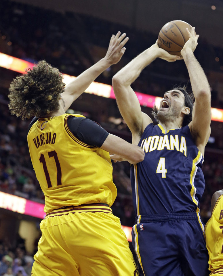 Photo - Indiana Pacers' Luis Scola (4), of Argentina, shoots over Cleveland Cavaliers' Anderson Varejao (17), of Brazil, during the fourth quarter of an NBA basketball game Sunday, Jan. 5, 2014, in Cleveland. The Pacers won 82-78.  (AP Photo/Tony Dejak)