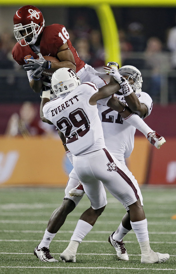 Oklahoma's Jalen Saunders (18) makes a catch over Texas A&M's Deshazor Everett (29) and Steven Terrell (21) during the college football Cotton Bowl game between the University of Oklahoma Sooners (OU) and Texas A&M University Aggies (TXAM) at Cowboy's Stadium on Friday Jan. 4, 2013, in Arlington, Tx. Photo by Chris Landsberger, The Oklahoman